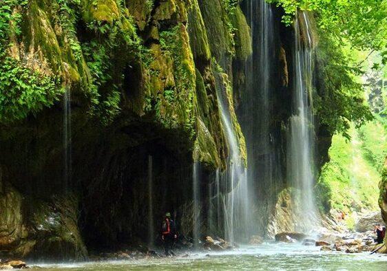 a man standing under a waterfall